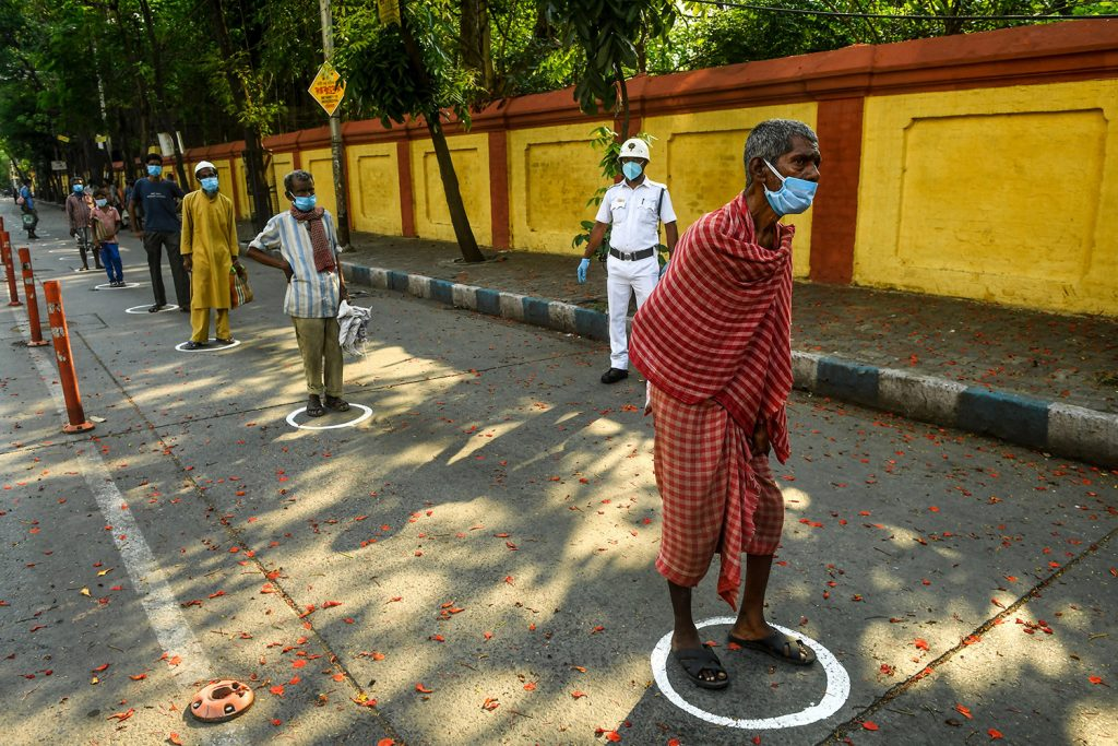 Slum dwellers stand in marked circles as they queue to receive relief material during a government-imposed nationwide lockdown as a preventive measure against the COVID-19 coronavirus, in Kolkata on April 30, 2020. (Photo by Dibyangshu SARKAR / AFP) (Photo by DIBYANGSHU SARKAR/AFP via Getty Images)